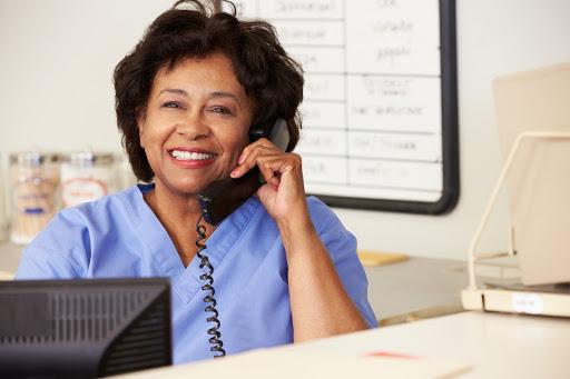 Nurse Making Phone Call At Nurses Station Smiling To Camera