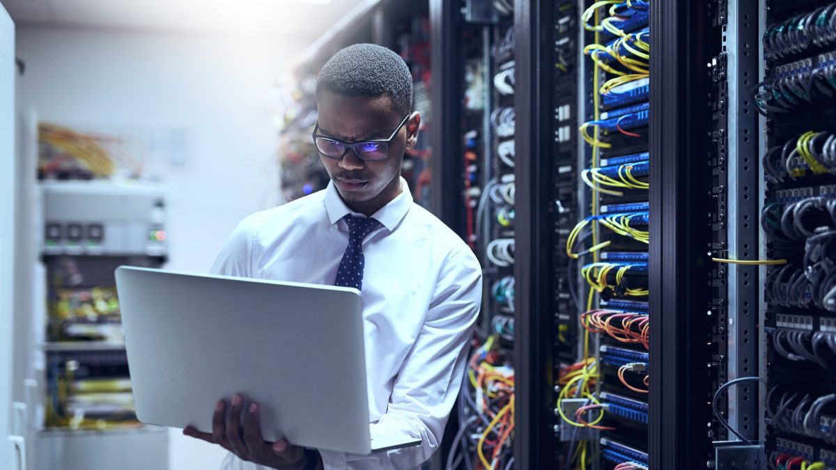 Shot of a fibre internet technician working on his laptop while standing inside of a server room