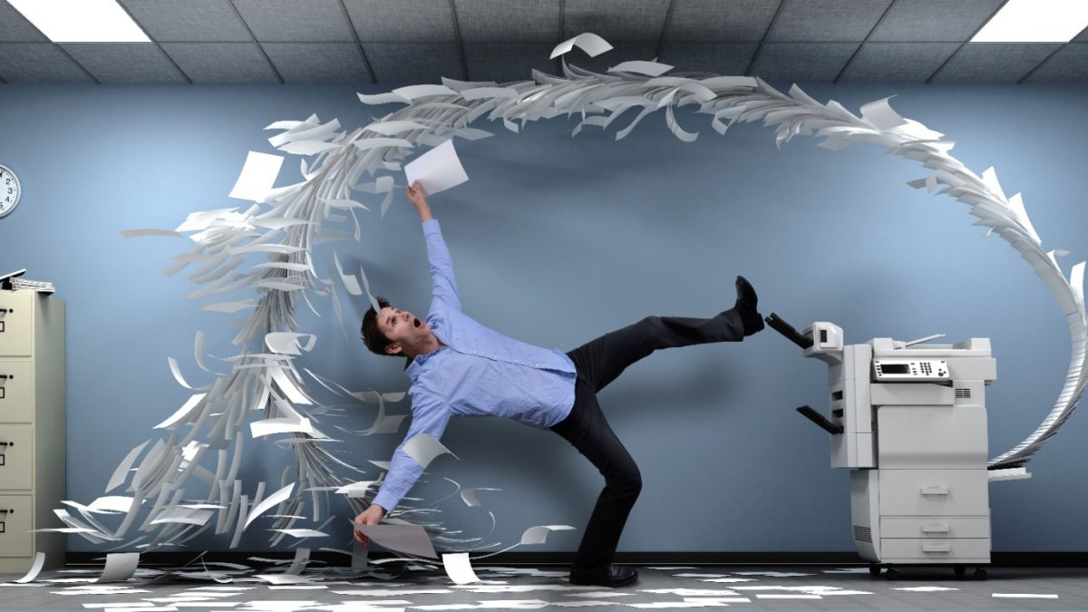 paper flying from an office printer while man ducks