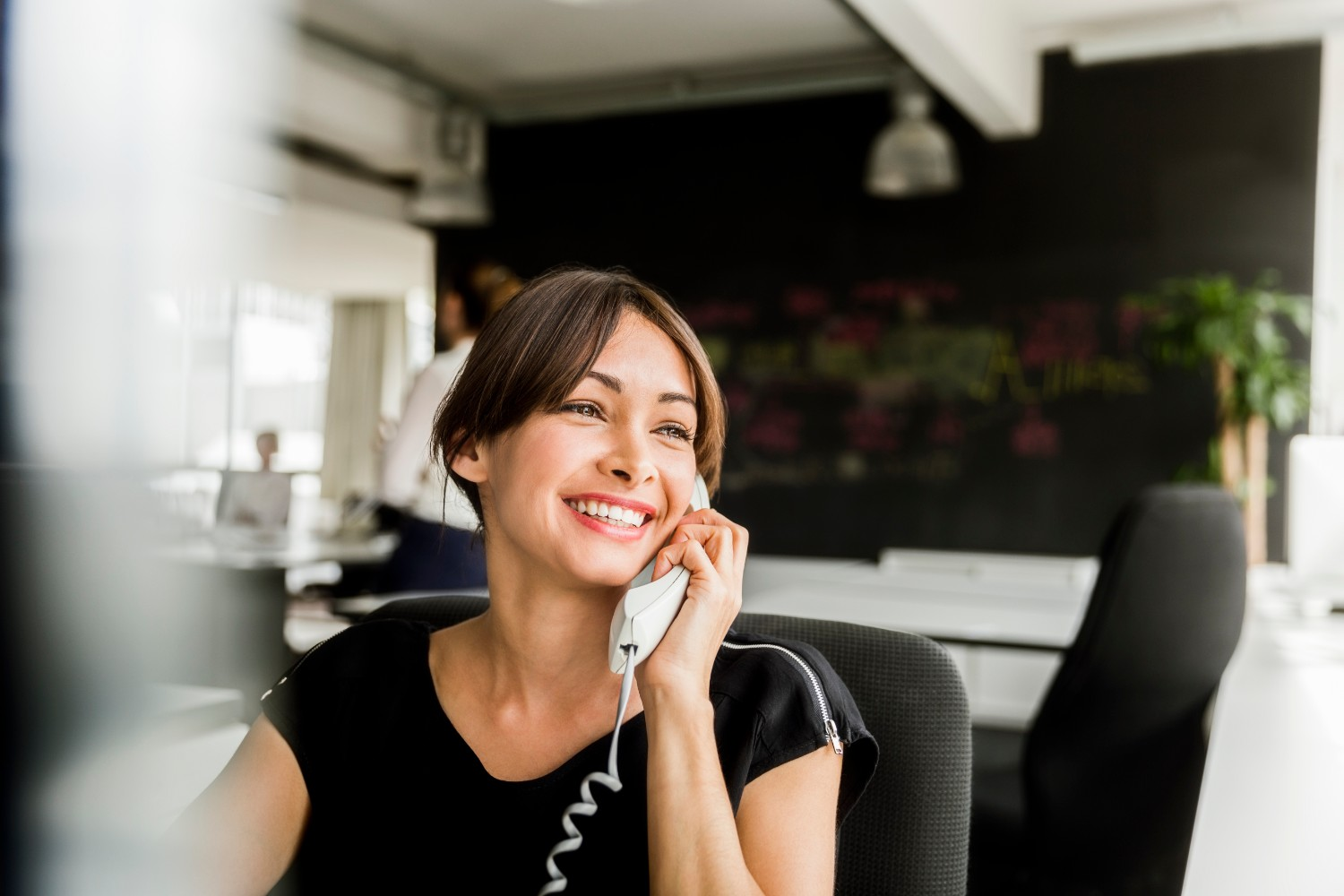 Cheerful businesswoman using VoIP phone in office. Happy female professional is looking away while sitting on chair. Beautiful executive is at brightly lit workplace.