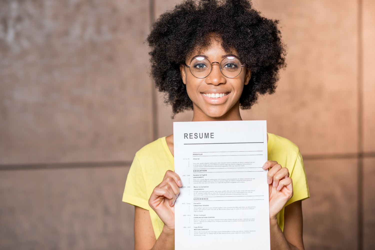 Woman holding a CV she's printed from an office printer