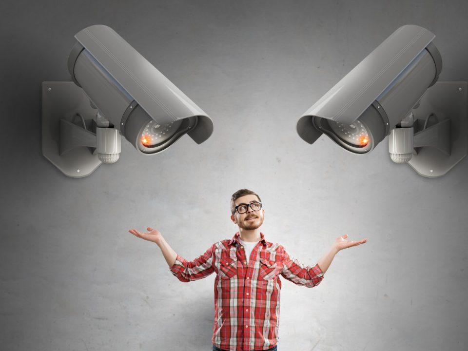 man in red checked shirt looking at CCTV camera