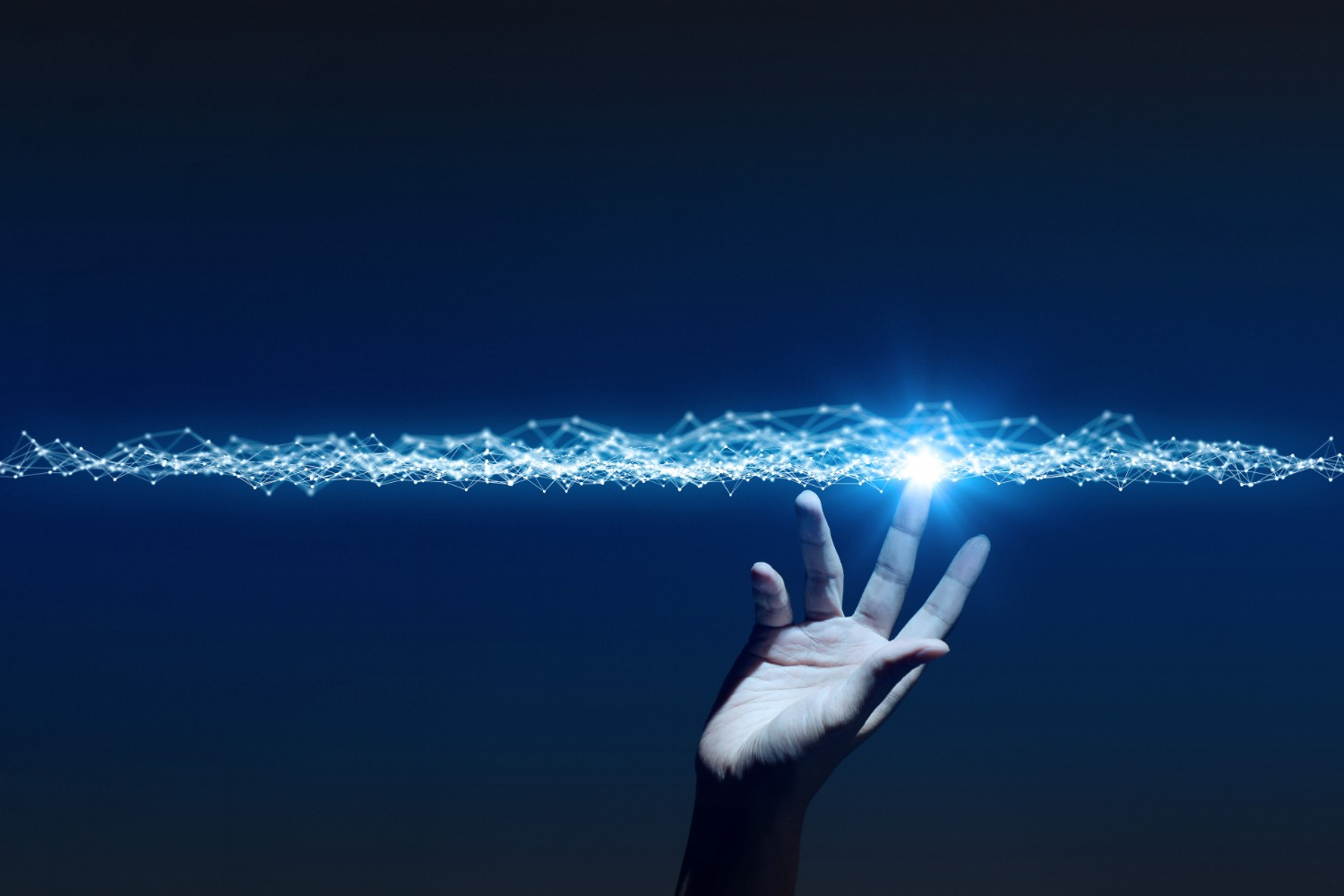 human hand reaching out to a beam of light, suggesting automation