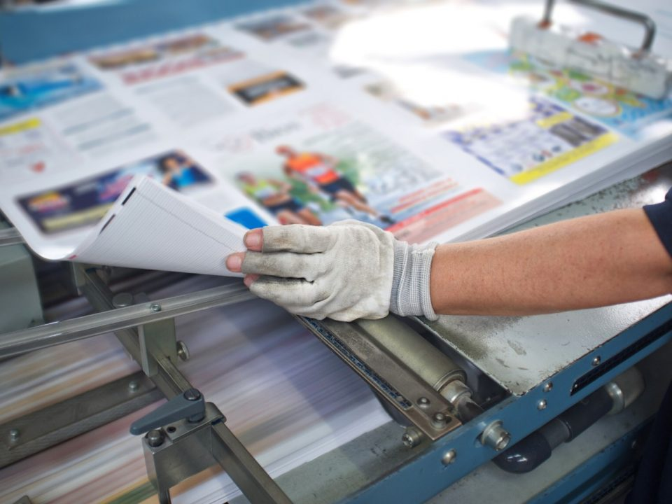 Person wearing a glove, manager a commercial printer