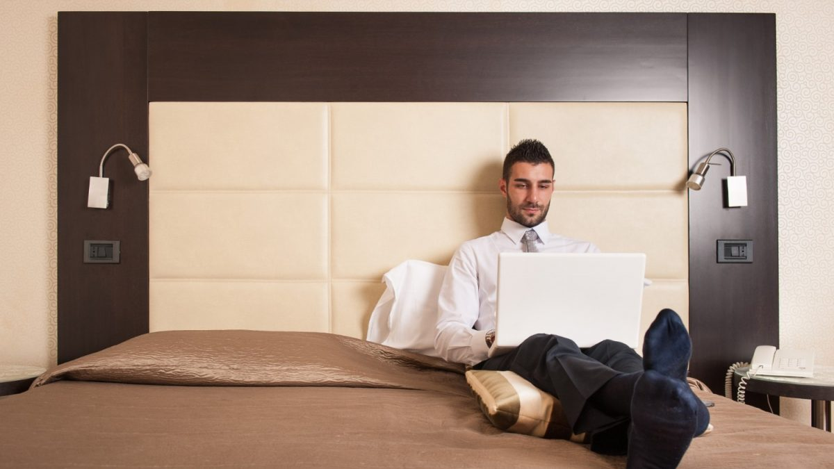 business man relaxing on bed using the hotel's wireless internet
