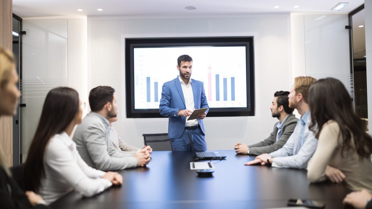 businessman leading an employee training session with a group of people