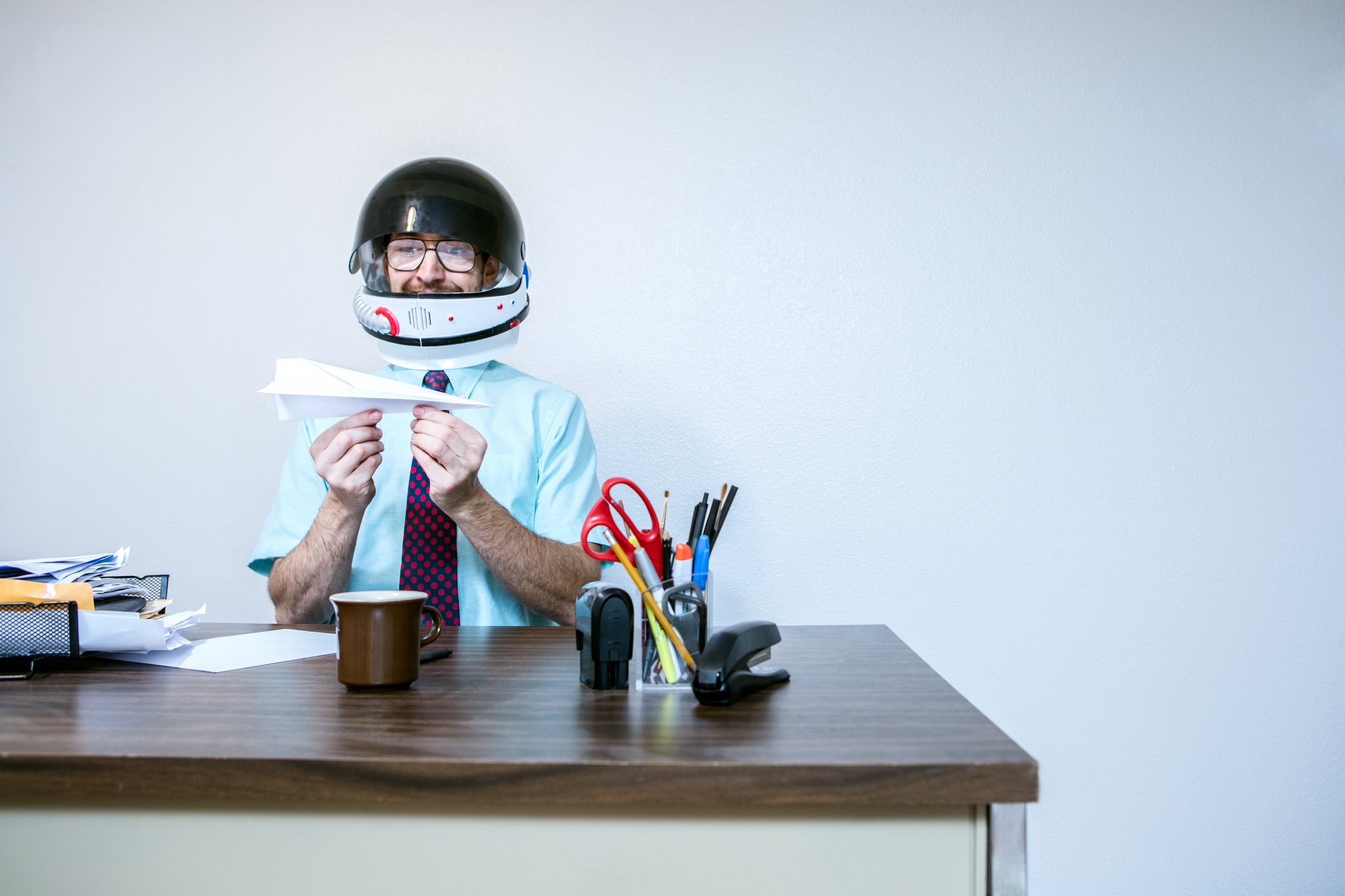 A business man working in the office imagines he is an astronaut, wearing a toy space suit helmet while sitting at his desk.