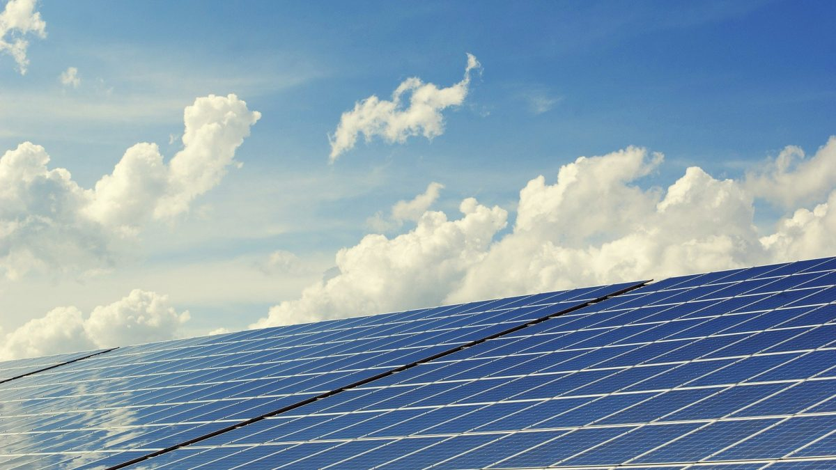 photovoltaic solar energy system with clouds in the background