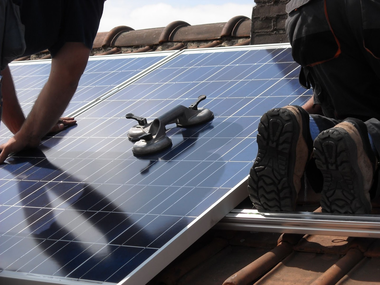 technicians installing solar panels on a roof
