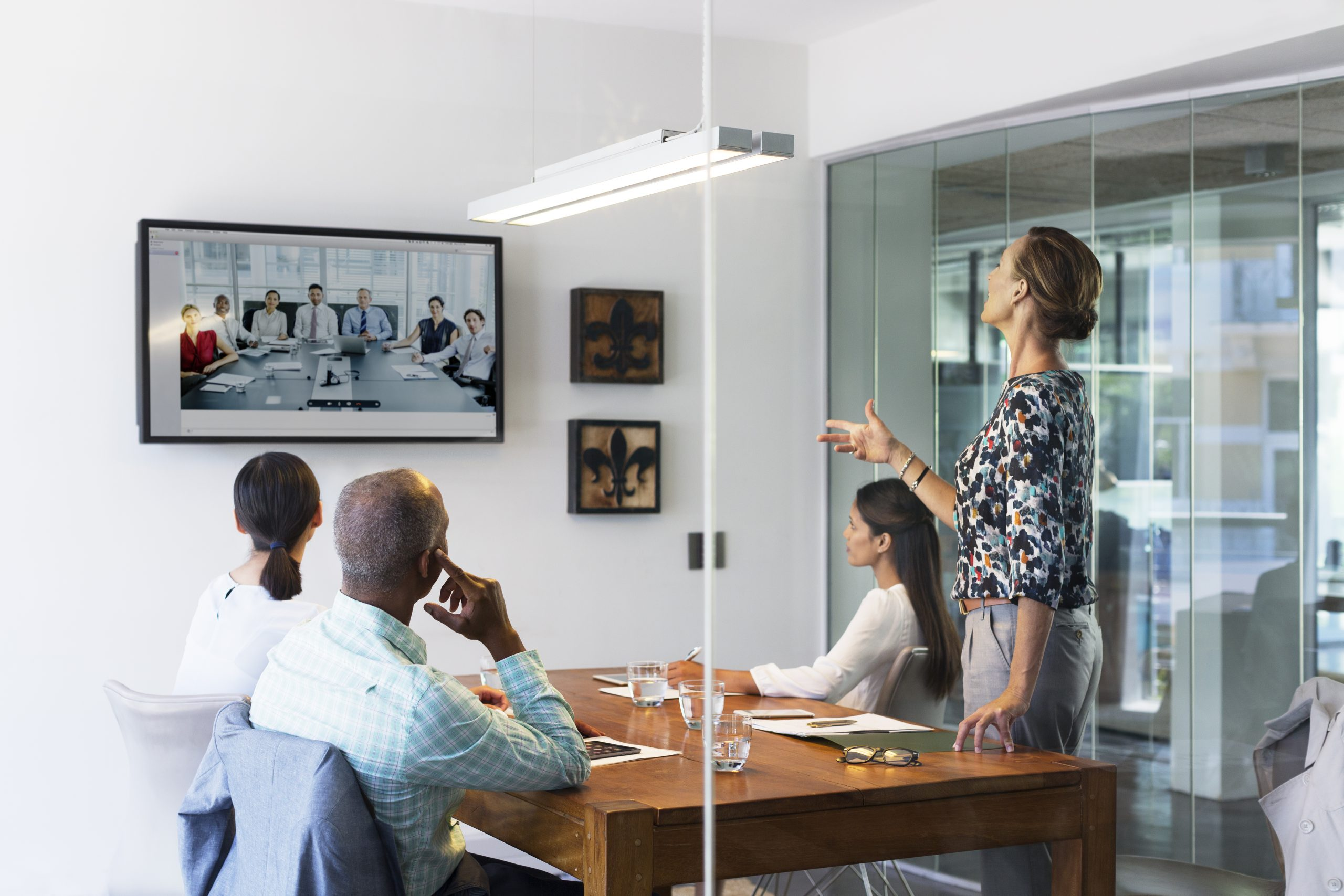 Multi-ethnic business people video conferencing at desk in a smart office board room