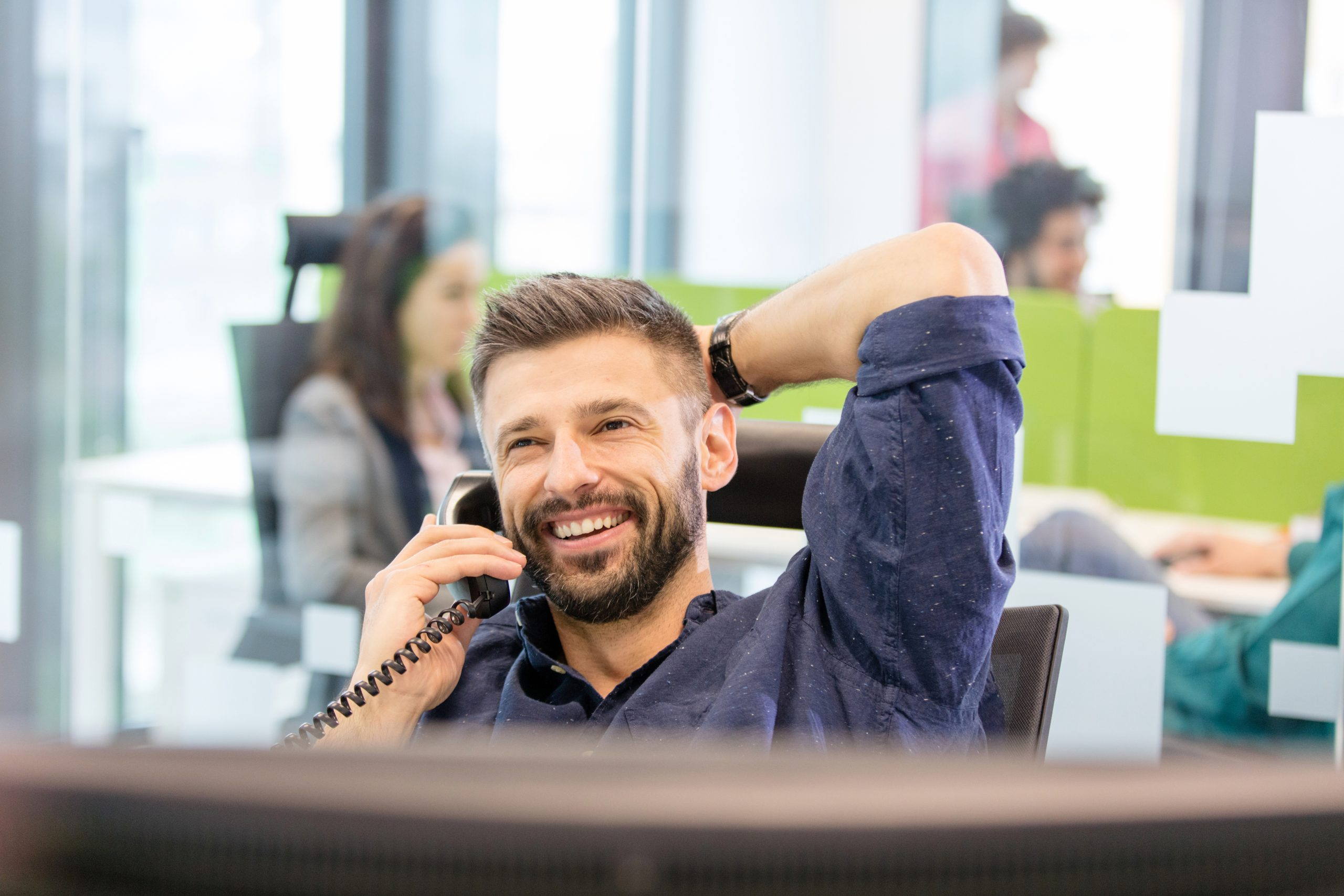 man in office talking on a VoIP phone.