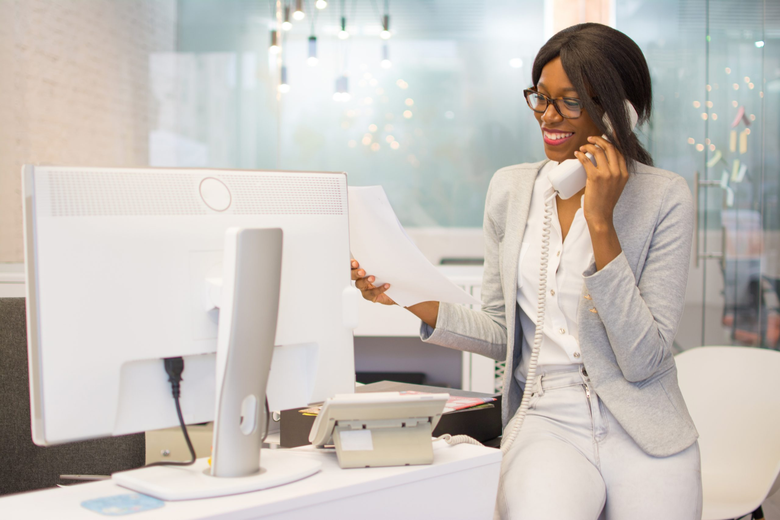 Young woman secretary working in modern office and talking on a VoIP phone.