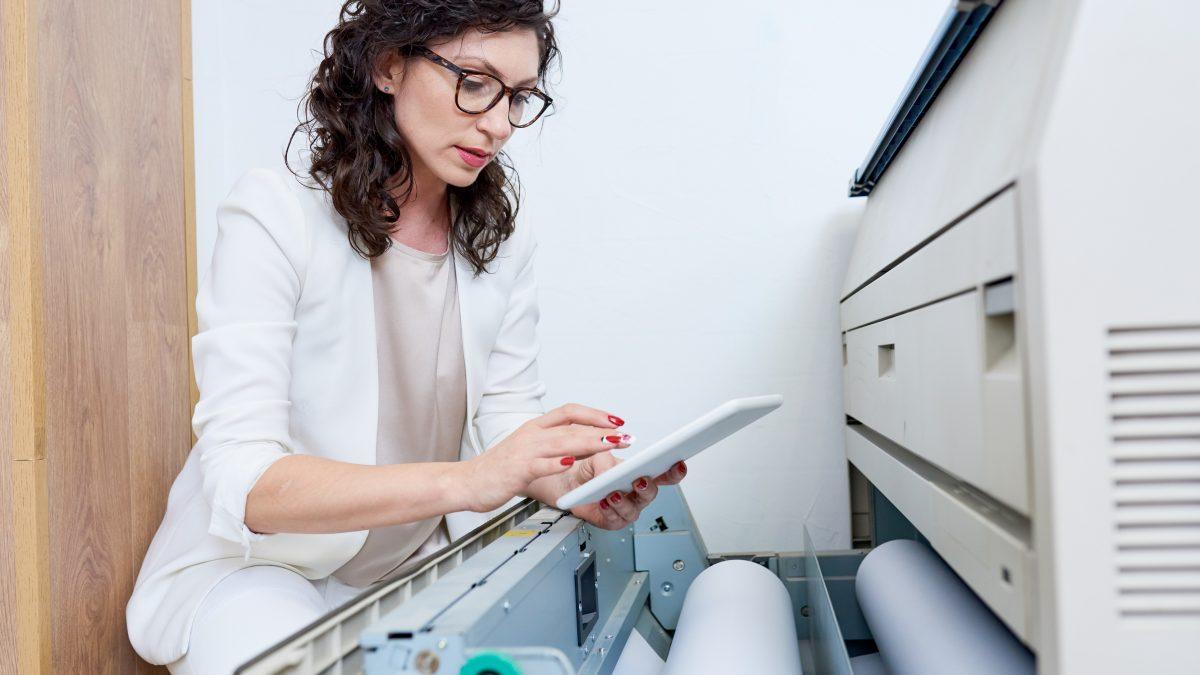 Side view portrait of graphic designer operating plotter machine via digital tablet in modern printing shop