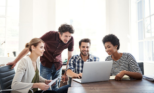 marketers gathered around a laptop discussing the digital customer experience.