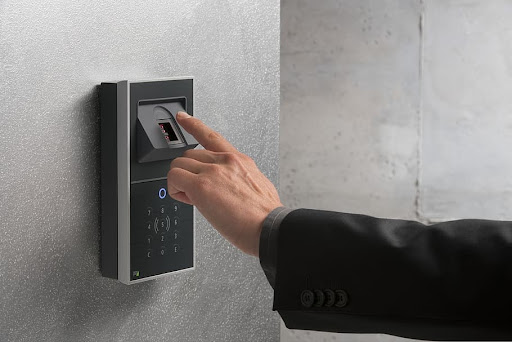 shot of a man pressing a finger on a biometric access control terminal.