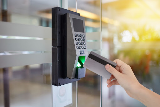 shot of a person holding an access card in front of an access control terminal.