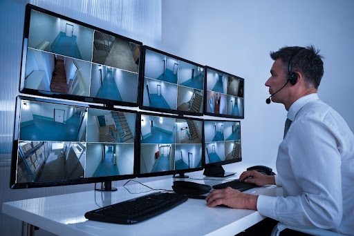 man wearing a headset sitting in front of CCTV monitors.